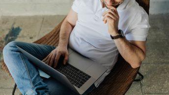 mężczyzna w białym t-shirt, w dżinsach z laptopem na kolanach